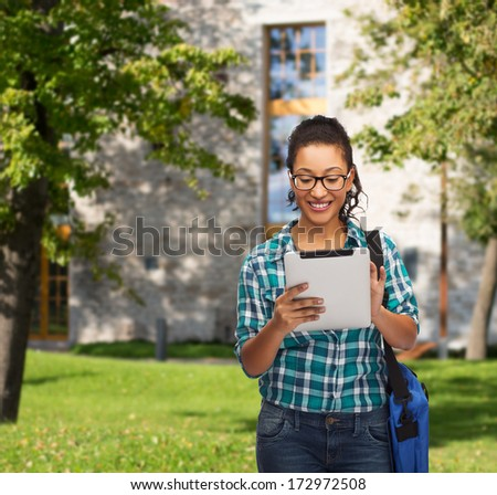education, technology and people concept - smiling female african american student in eyeglasses with tablet pc and bag - stock photo