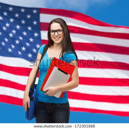 education, technology and people concept - smiling student in black glasses with bag, folders and tablet over american flag background