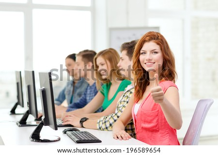 education, technology and school concept - smiling female student with classmates in computer class at school showing thumbs up - stock photo