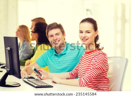 education, technology and school concept - smiling student with smartphone in computer class - stock photo