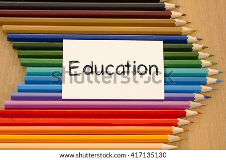 Education text concept and colored pencil on wooden background - stock photo