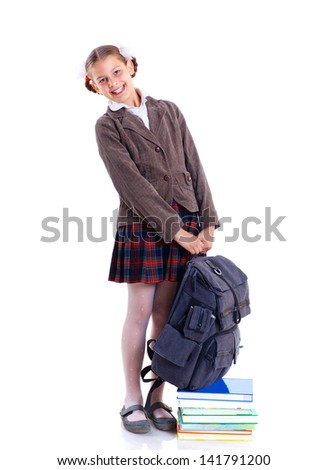 Education theme. Joyful schoolgirl smiling happily with heavy backpack and book. Isolated on white background