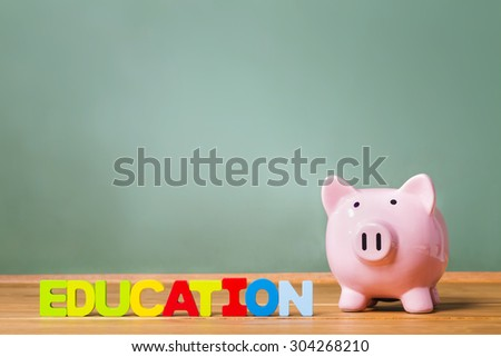 Education theme with piggy bank and green chalkboard background - stock photo