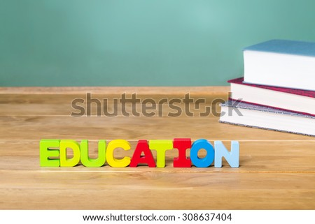 Education theme with textbooks and green chalkboard background - stock photo