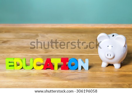 Education theme with white piggy bank and green chalkboard background - stock photo
