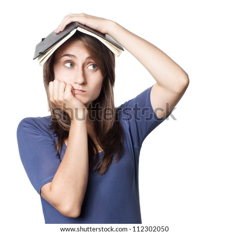 Education. Tired girl holds a notebook on her head on a white background with copyspace - stock photo