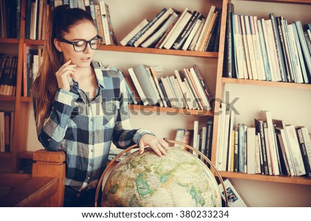 Education travel and geography concept. Hipster lovely woman female student in blue glasses in library with globe. Instagram filter - stock photo