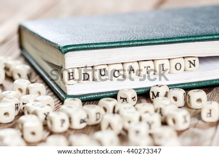 Education word written on a wooden block in a book. On old wooden table.