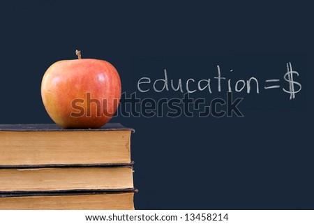 education = $ written on blackboard with apple, books - stock photo