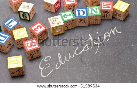 Education Written Out on Chalk Board with Toy Blocks - stock photo