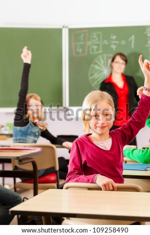 Education - Young female teacher with pupil in his form of the elementary or primary school teaching