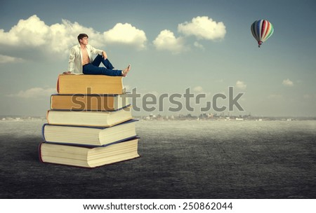 Education. Young man sitting on a pile of books in the open air. - stock photo