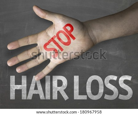 Educational and Creative composition with the message Stop Hair Loss on the blackboard - stock photo