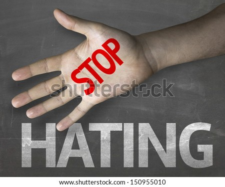 Educational and Creative composition with the message Stop Hating on the blackboard - stock photo