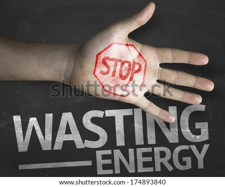 Educational and Creative composition with the message Stop Wasting Energy on the blackboard - stock photo