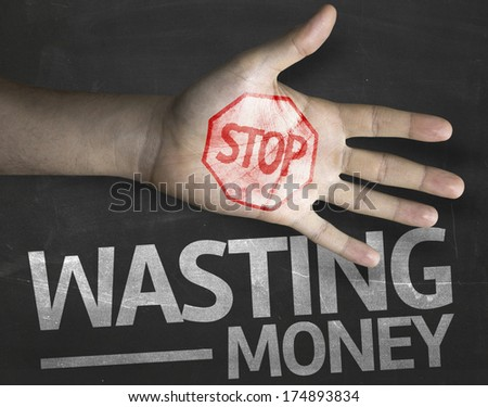 Educational and Creative composition with the message Stop Wasting Money on the blackboard - stock photo
