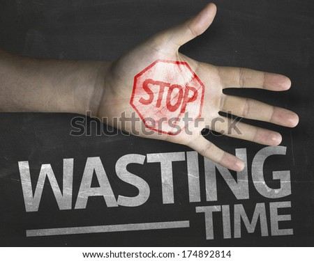 Educational and Creative composition with the message Stop Wasting Time on the blackboard - stock photo