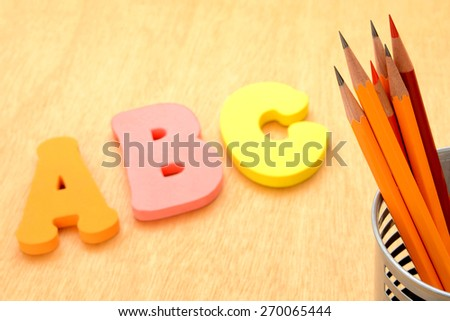 Educational concept, pencils and alphabet toy - stock photo