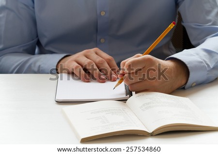 Educational concept. Student writing in a notebook and preparing for the exams - stock photo