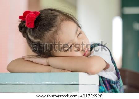 Educational theme: schoolgirl sleeping on her textbooks in a school - stock photo
