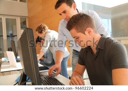 Educator helping student in training class - stock photo