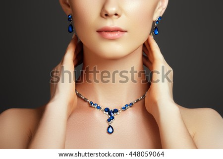 Eegant fashionable woman with jewelry. Beautiful woman with a sapphire necklace. Beauty young model with a diamond pendant on a gray background. Jewellery and accessories