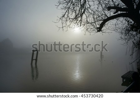 Eerie landscape with a bridge over a river in fog - stock photo