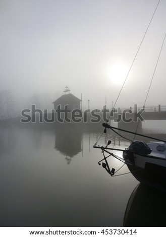 Eerie landscape with a bridge over a river in fog with sail boat silhouette in front - stock photo