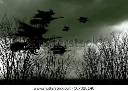 Eerie surreal silhouette of a swarm of witches on broomsticks flying across a spooky landscape with dead trees for Halloween concept. - stock photo