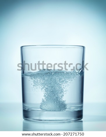 effervescent dissolving fizzy tablet in water glass - stock photo