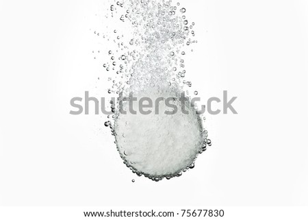 Effervescent tablet in water with bubbles - stock photo