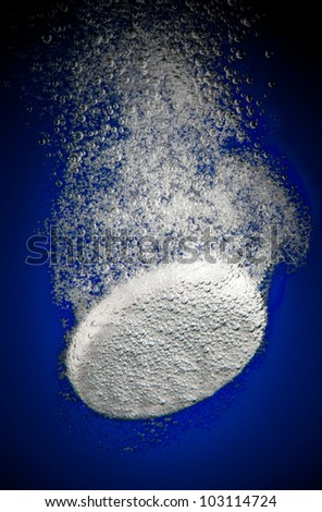 Effervescent tablet in water with bubbles on a blue background - stock photo