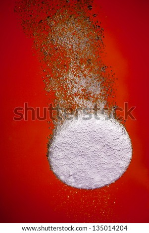 Effervescent tablet in water with bubbles on a red background - stock photo