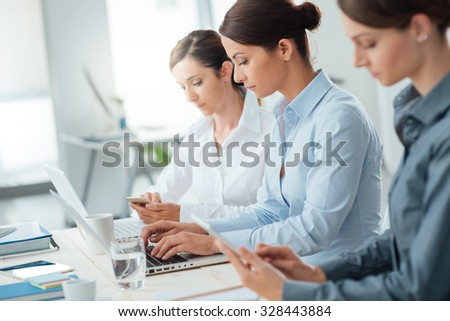 Efficient business women working together at office desk using laptops and mobile devices, women entrepreneurs concept