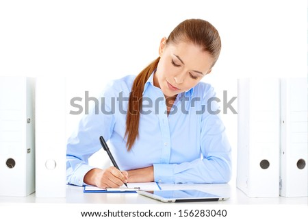 Efficient businesswoman working at her desk sitting writing notes from a tablet computer surrounded by neat rows of office files - stock photo