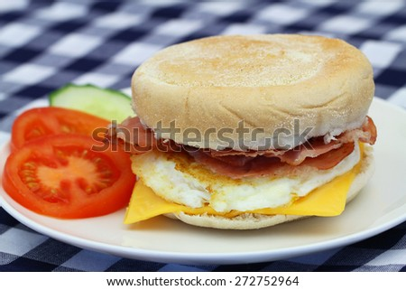 Egg and bacon muffin with slices of tomato and cucumber on checkered cloth with copy space