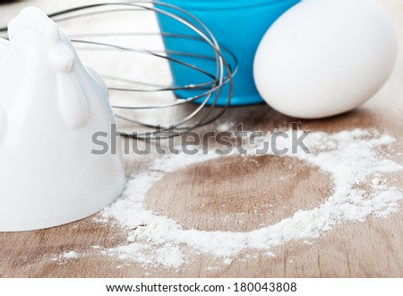 Egg and flour raw food on wooden cutting board - stock photo