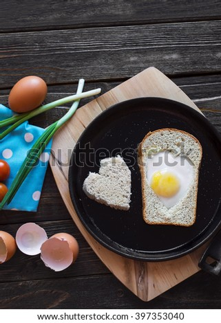 Egg baked in a bread in a heart shape on a cast iron skillet. Fried eggs. A hearty breakfast in a rustic style. Top view. - stock photo