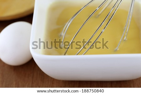 Egg beater in a kitchen with cooking ingredients - stock photo