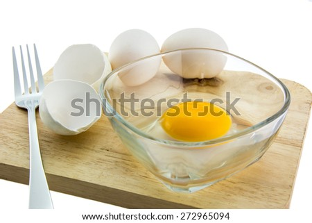 Egg in a glass bowl and egg shells, over white background