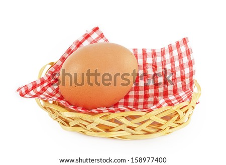 egg in wicker basket with a checkered napkin isolated on white background