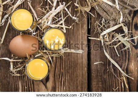 Egg Liqueur (close-up shot) on wooden background - stock photo