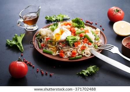Egg noodles with fried vegetables on a plate of brown clay. Next to spices and herbs.