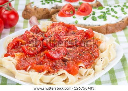 Egg noodles with ketchup, tomatoes, and sandwich