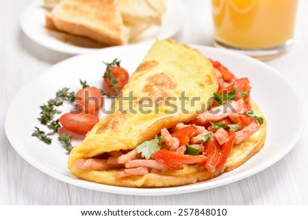 Egg omelette with vegetables and ham on white plate, close up view - stock photo