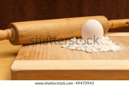 Egg on Top of Flour Pile with Rolling Pin - stock photo