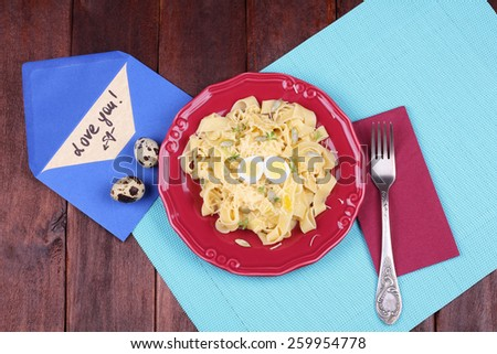 Egg pasta with quail egg, watercress salad and seeds. Dish pasta and coleslaw on the table. Delicious hearty lunch. Surprise for dear person. Top view. Pasta dish. Love letter, Declaration of love. - stock photo