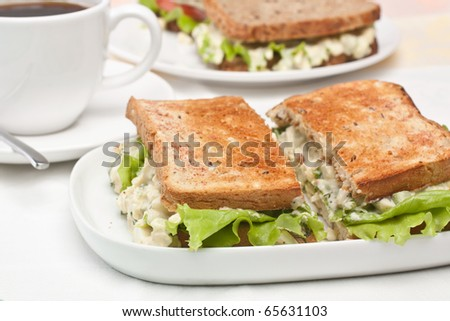 egg salad sandwiches on toasted bread and a cup of coffee - stock photo