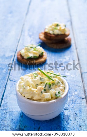 Egg salad with chives on a wooden background. Selective focus.