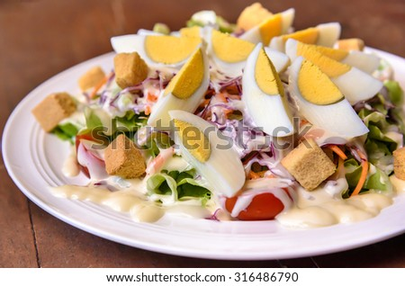 Egg salad with vegetable on wooden table